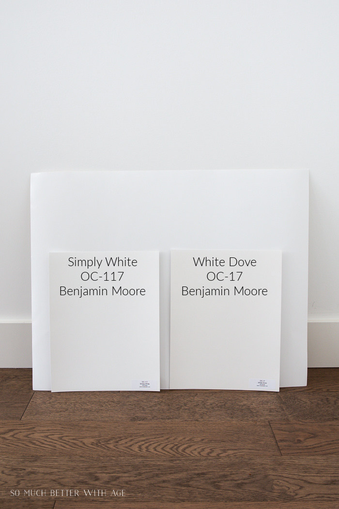 Simply White and White Dove by Benjamin Moore paint colors leaning against a wall and hardwood floors.