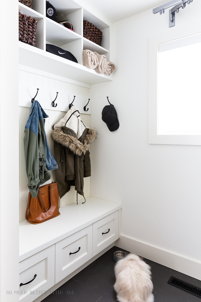 White laundry room with hooks for jackets.