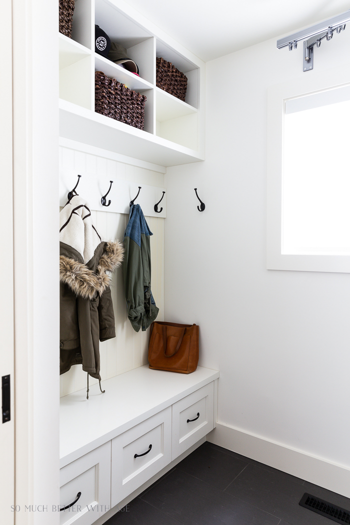 White cubbies and black hooks cloak room in laundry room.