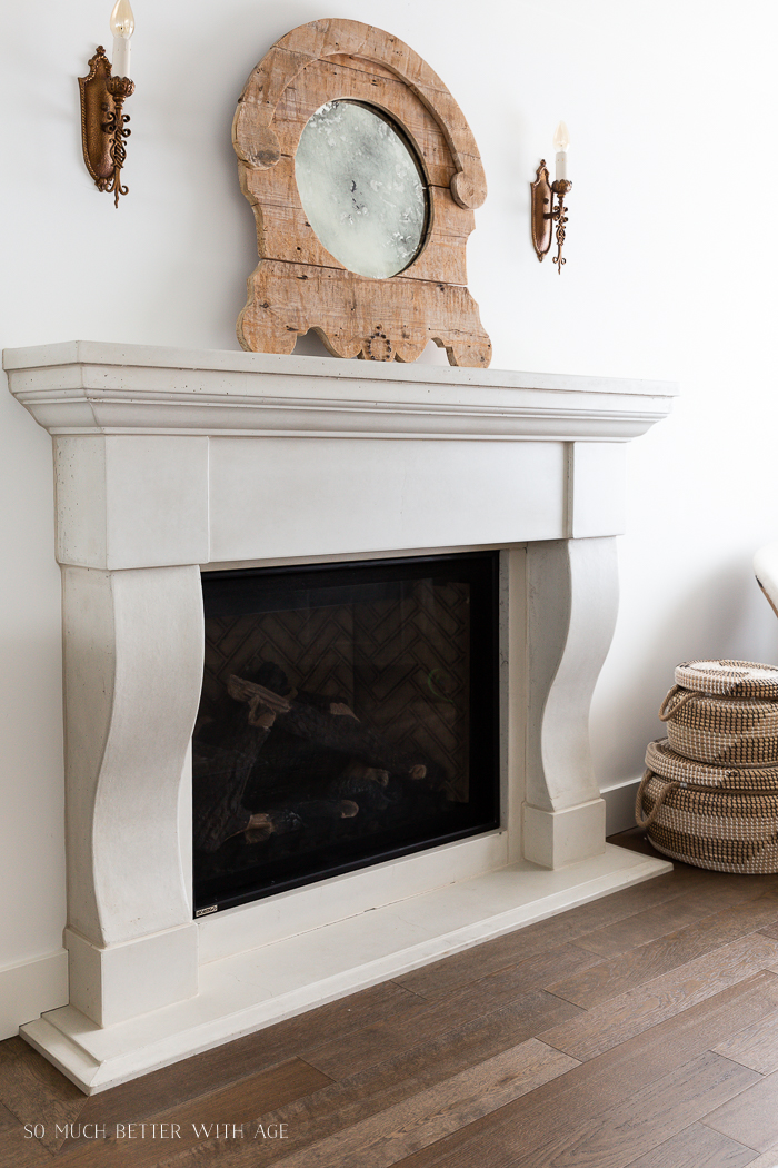 Cast stone fireplace with wooden rustic mirror sitting on mantel and two antique brass light sconces.