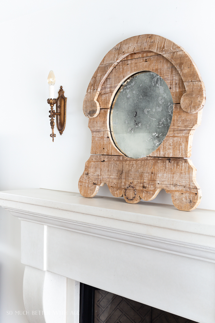 Wooden mirror on fireplace mantel and an antique sconce.