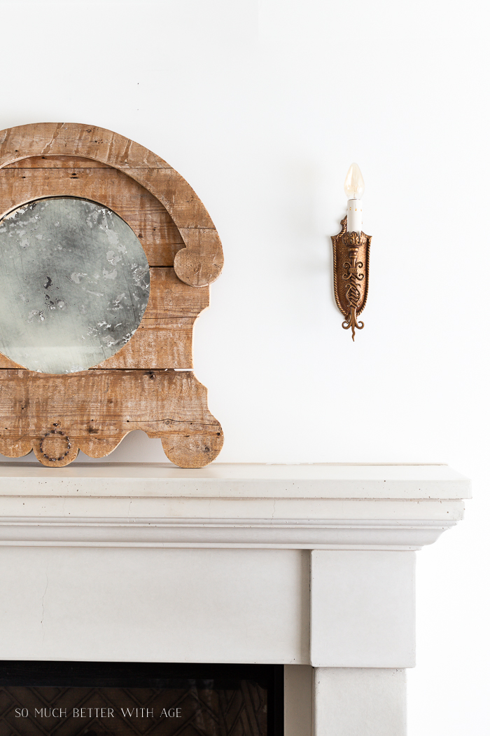 Wooden mirror and antique sconce above fireplace.