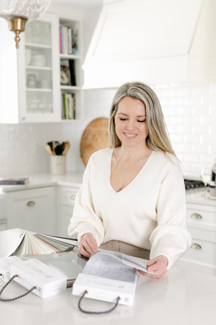 Woman looking at fabric and paint samples in a white kitchen.