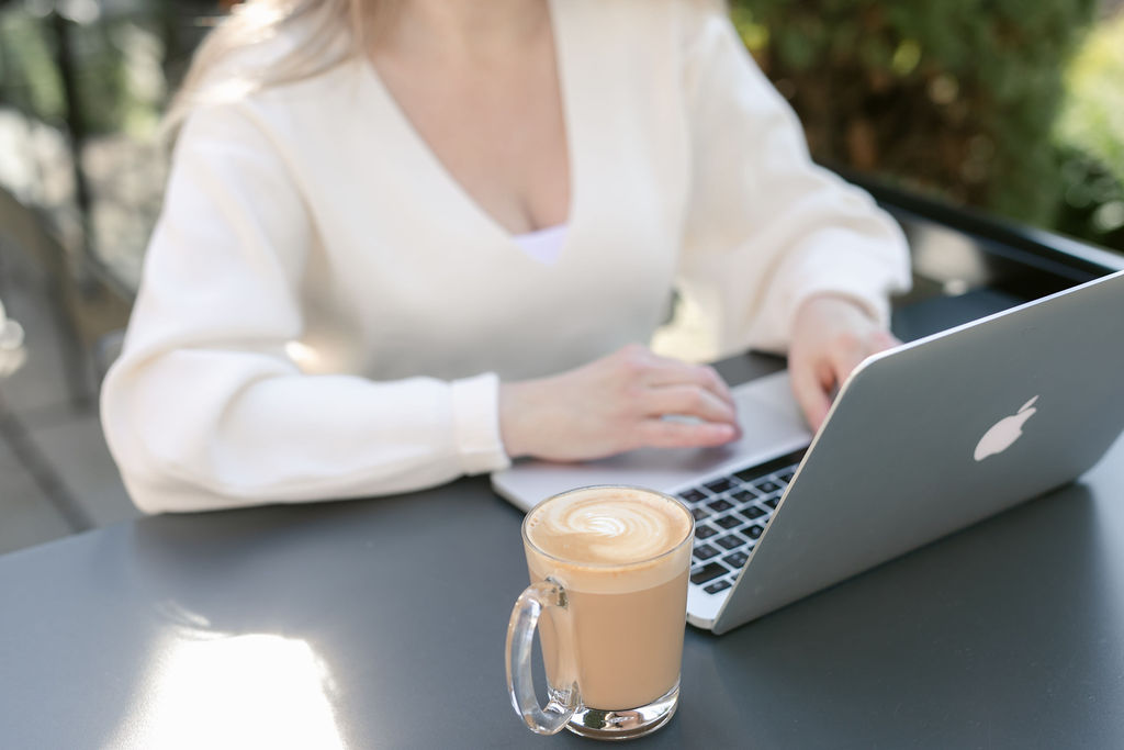 Woman sitting at a table with her laptop in a cafe.