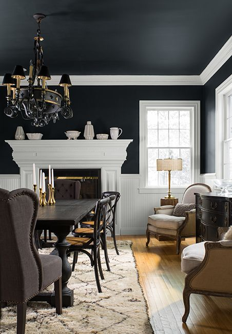 A formal dining room with the walls painted black and white.