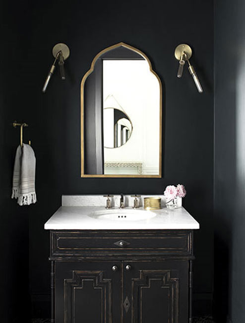A bathroom with dark walls and cabinet.