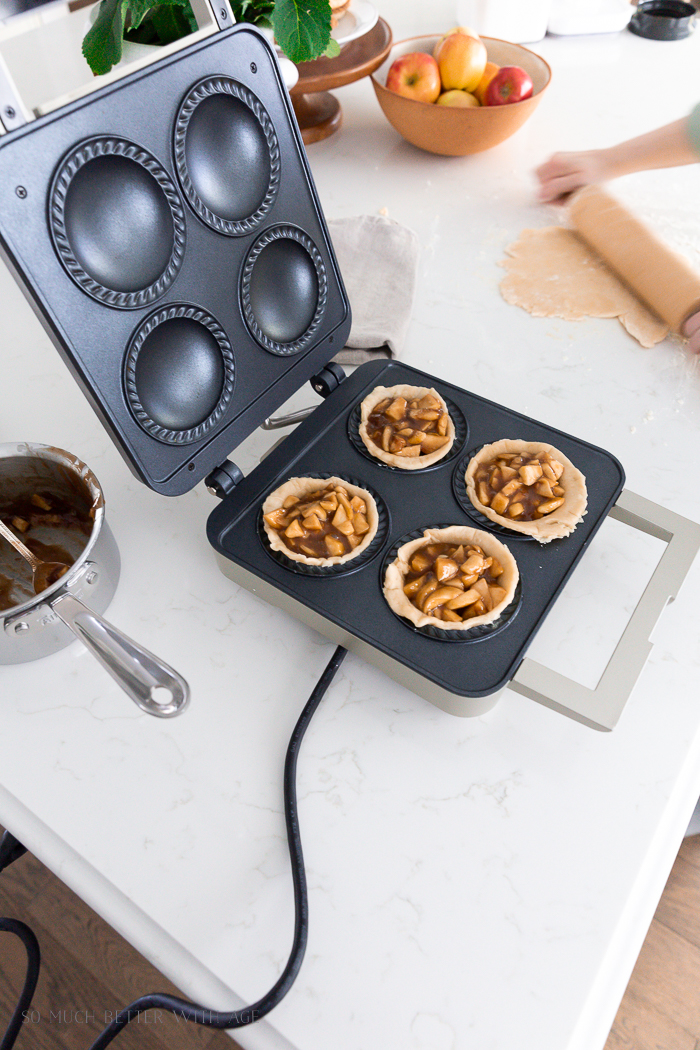 Mini pie maker with apple pies in it.