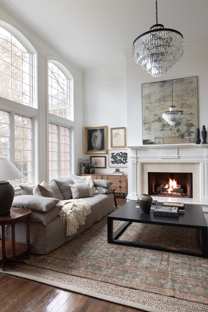 Haus Love living room with chandelier, vintage art, sofa, black coffee table and layered rugs.