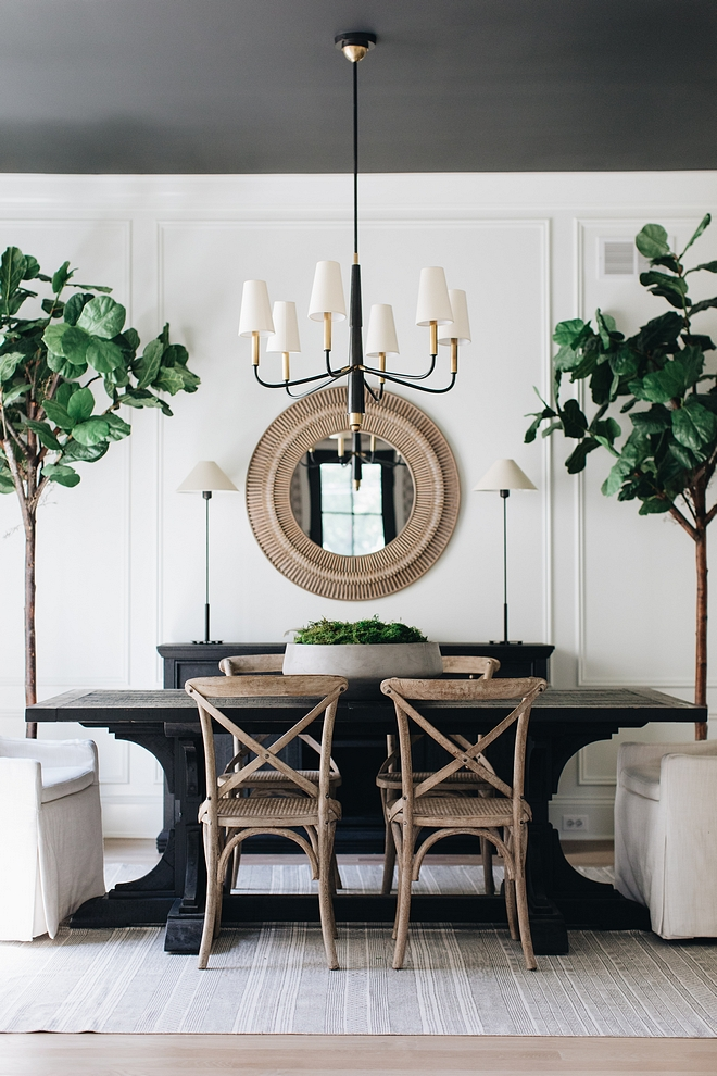 A wooden dining room table painted black with small trees beside it.