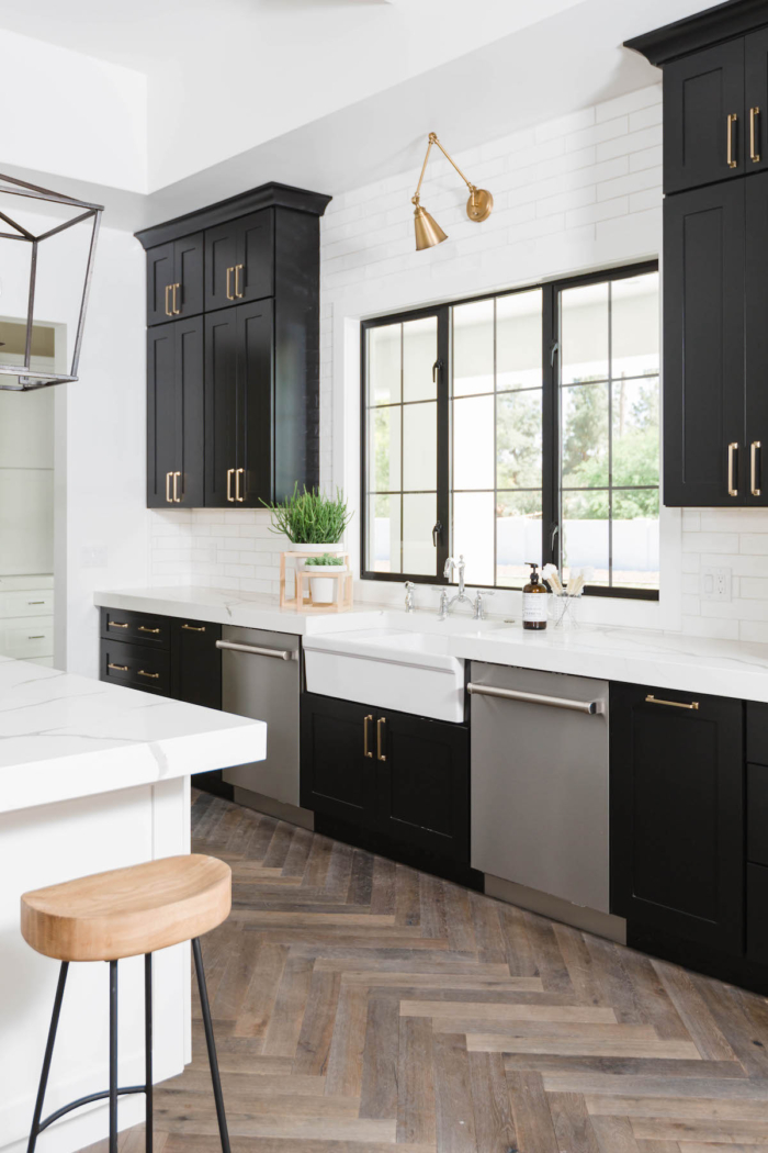 A white and black kitchen with the cupboards painted black.