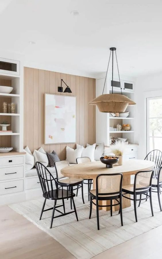Mindy Gayer Design dining room with black chairs, light wood table and rug.