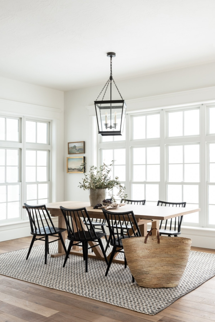 Studio McGee white dining room with black chairs and large rug.
