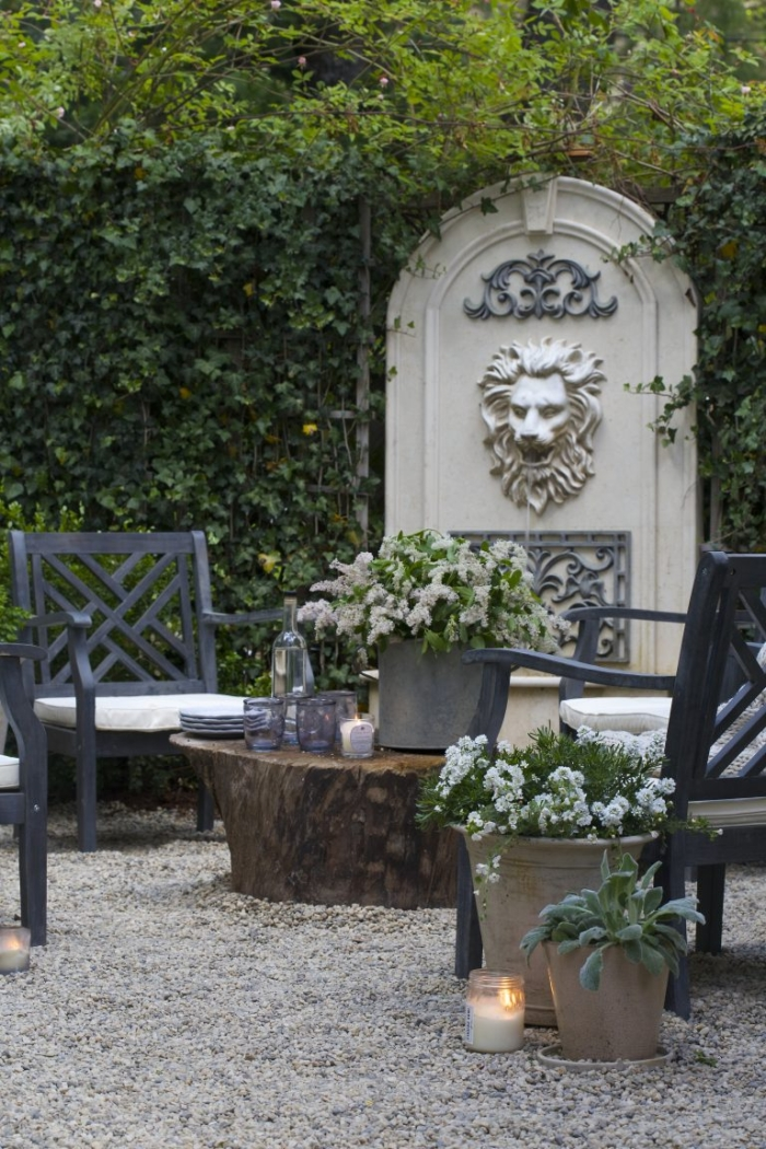 French water fountain with lion in beautiful back yard.