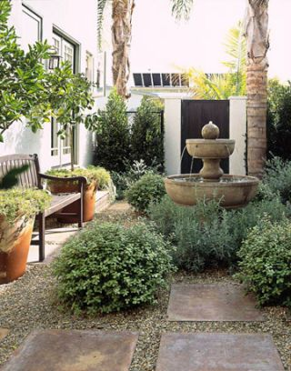 Water fountain and shrubs in courtyard.