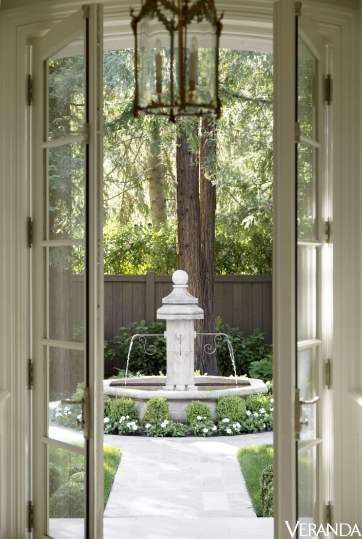Image of water fountain through French doors into a back yard.