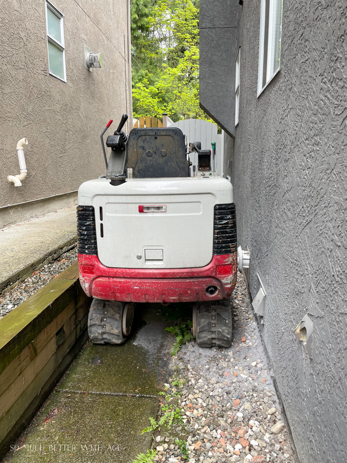 Small excavator going down side of house.