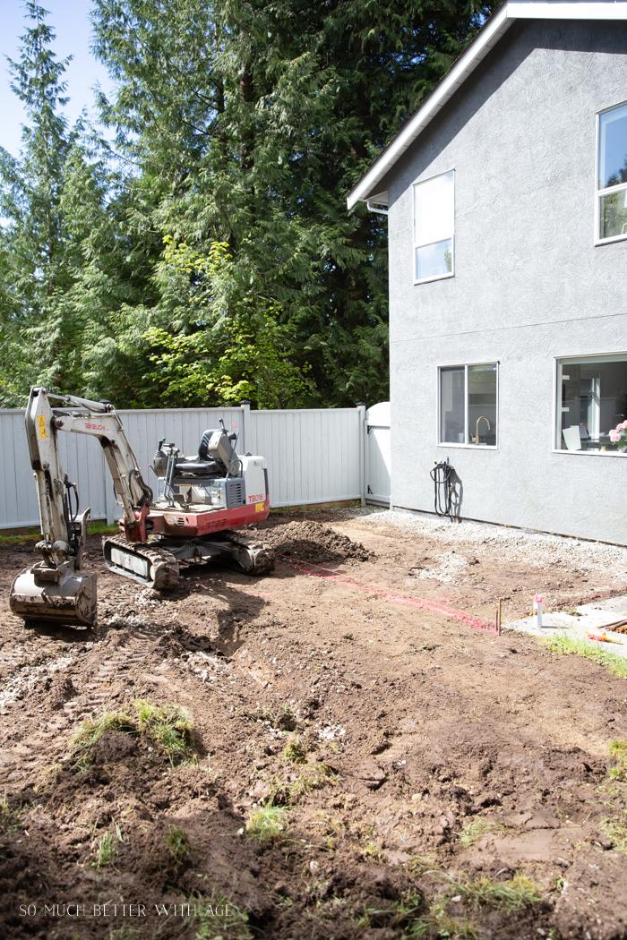 Excavator grading back yard.