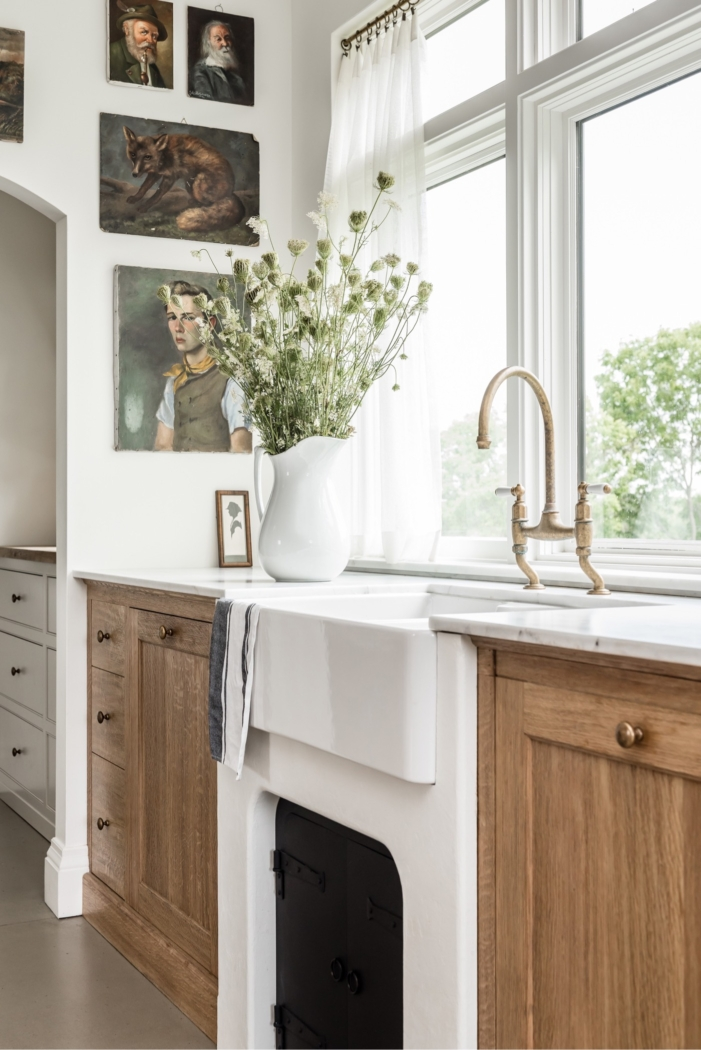 Wooden kitchen cabinets with white countertops and white walls by Angela Wheeler.