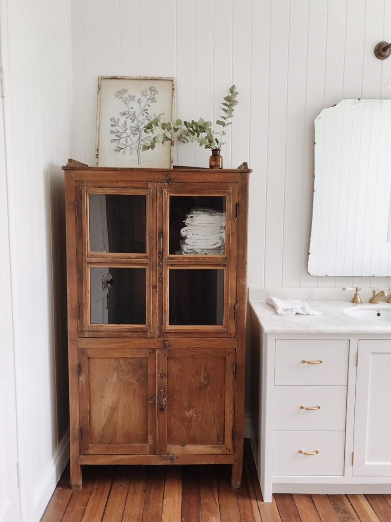 Wooden vintage cabinet in white bathroom.