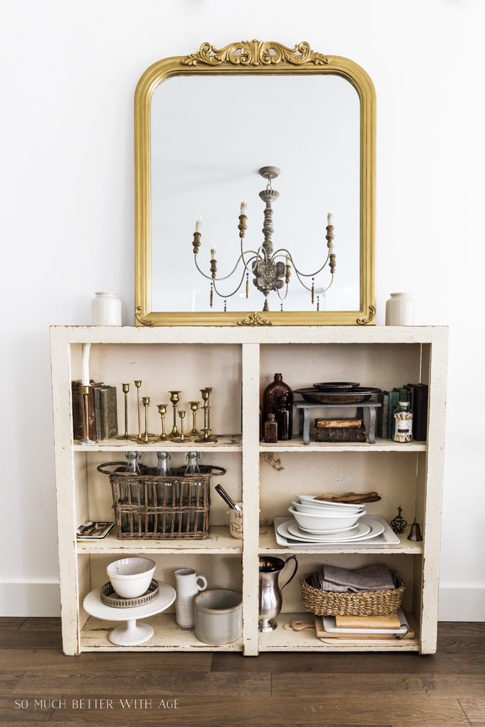 Collection of vintage items on old bookshelf with large French gold mirror leaning on top.