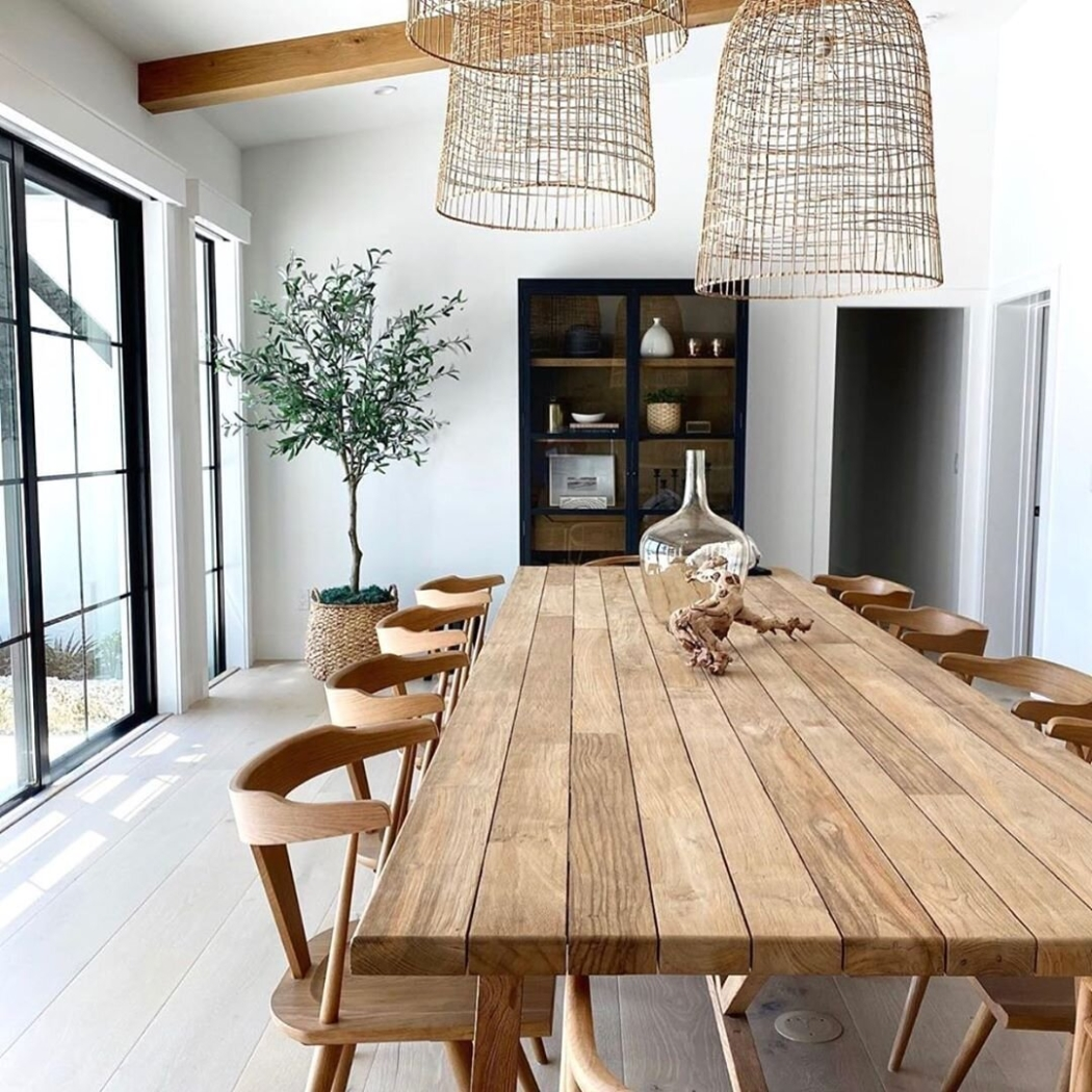 Huge wooden dining table in white room with vaulted ceiling and basket pendant lights.