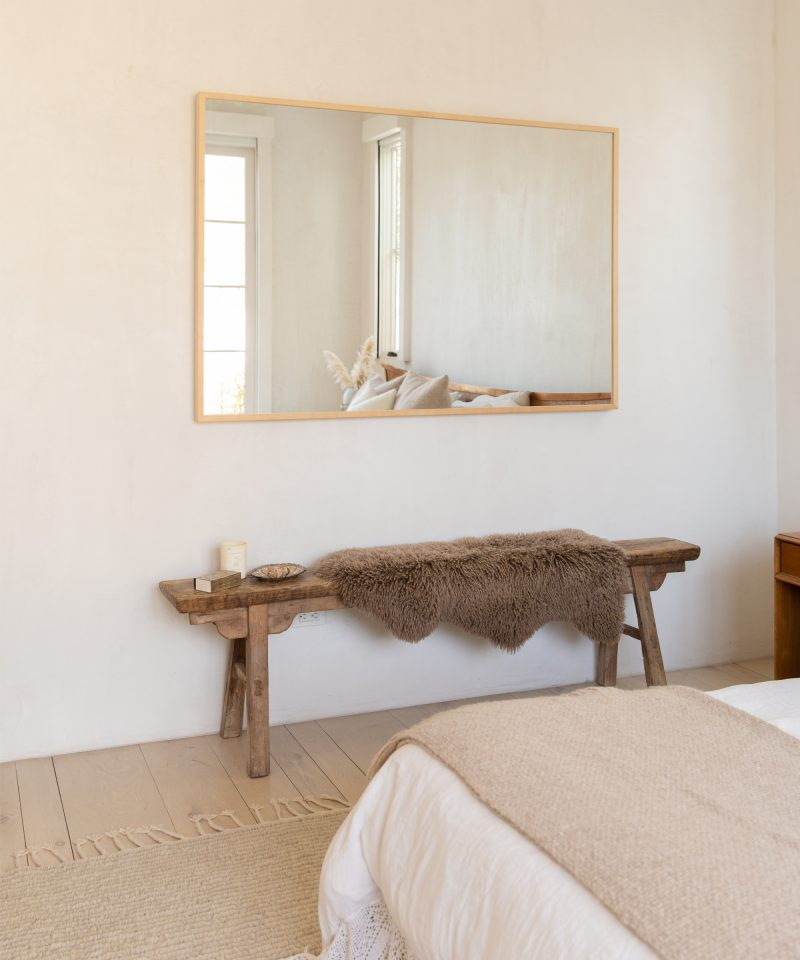 Neutral bedroom with white bedding, cream walls and wooden bench by Jenni Kayne.
