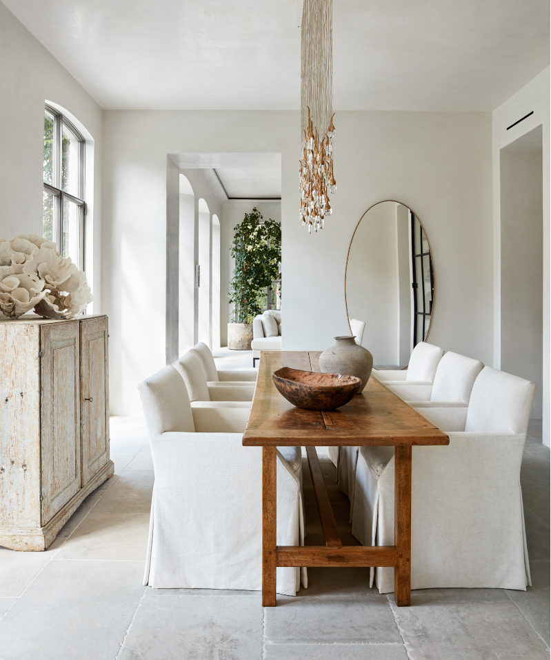Wooden dining table and white slipcovered chairs by Laura Resen Photography.