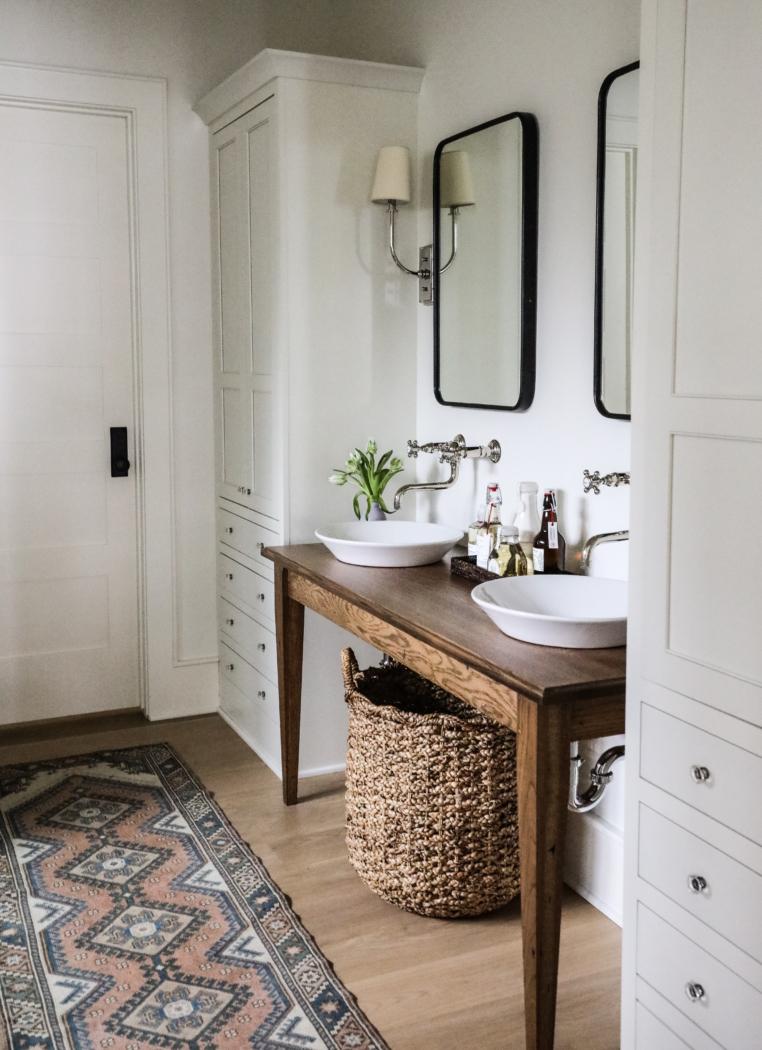 Wooden table for bathroom vanity, vintage rug and large basket under vanity.