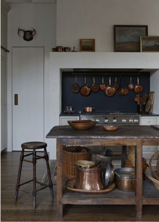 Modern French country kitchen with white textured walls and antique wooden island by Sabbe Interiors.