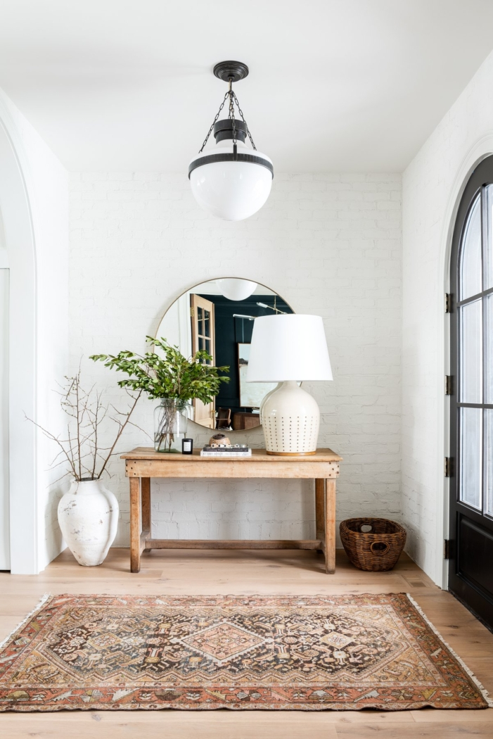 White foyer with black door with wood console table and vintage rug by Studio McGee.