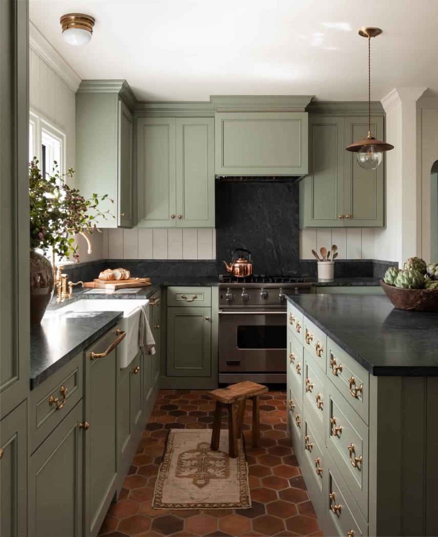 Green kitchen cabinets with mini gold light fixtures by Heidi Caillier Design.