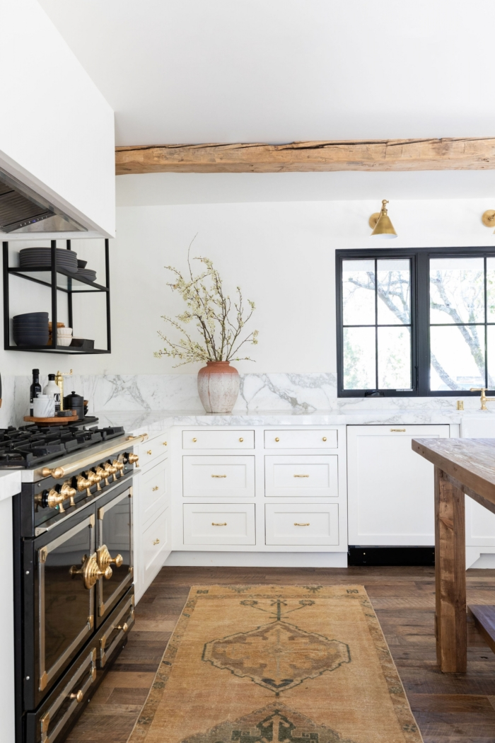 Large white kitchen with black accents and mini gold light fixtures by Design Shop Interiors.