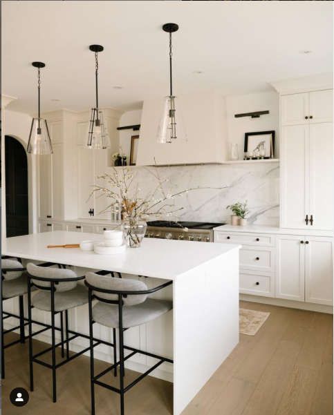 Trio of black and glass mini light fixtures in white kitchen by Heirloom Projects.