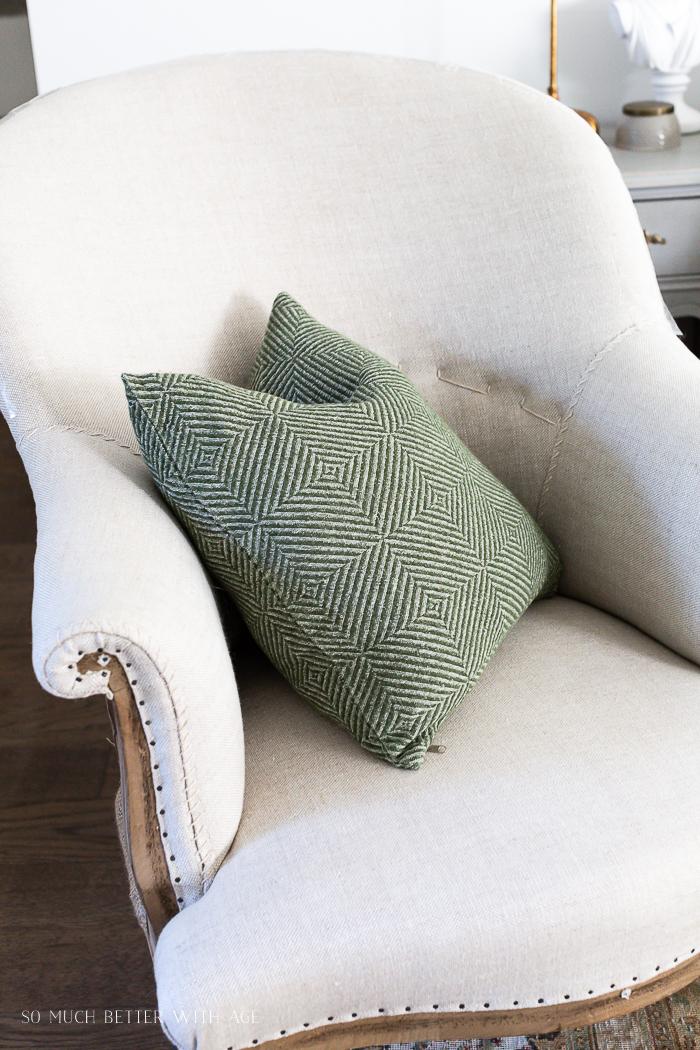 Linen deconstructed chair with green pillow.