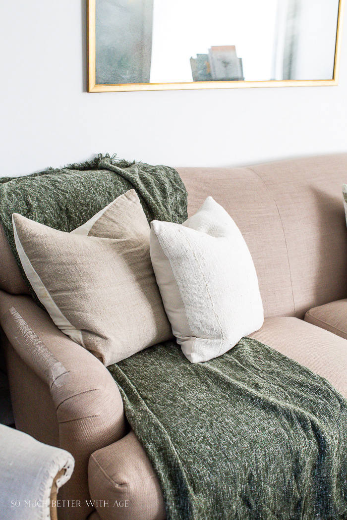 Green throw blanket over sofa with two neutral throw pillows.
