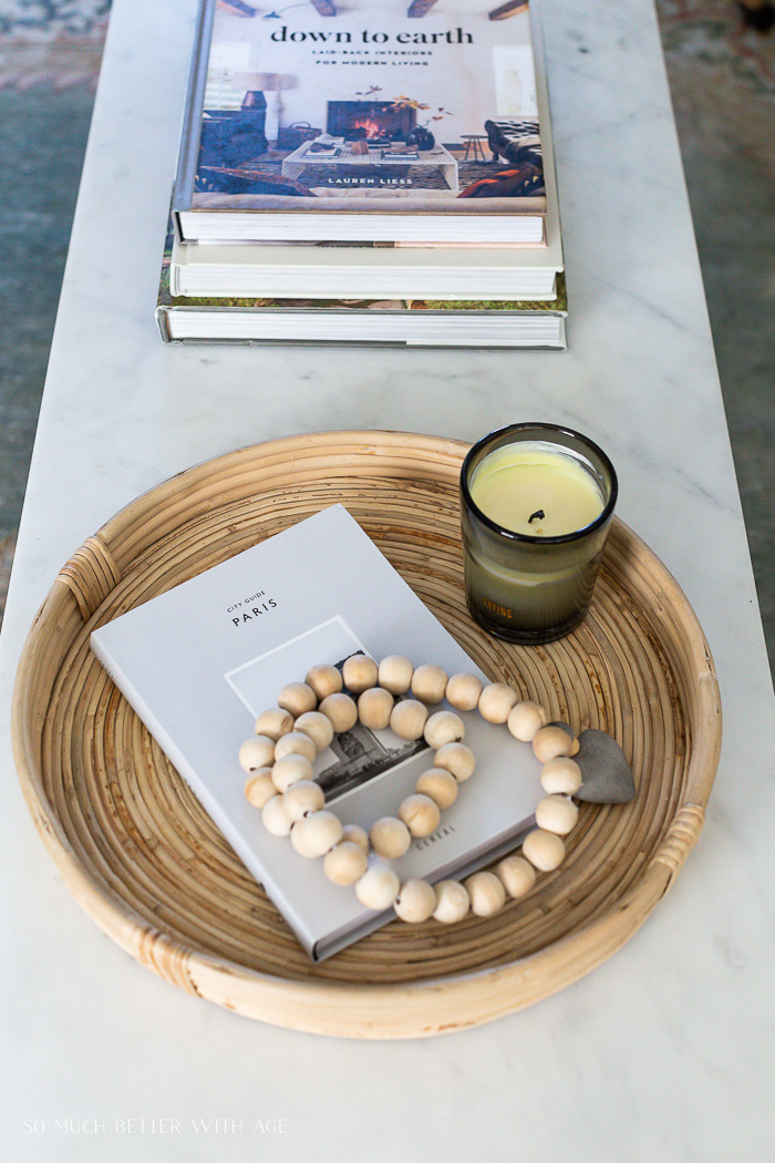 Rattan circular tray on marble coffee table with Down to Earth coffee table book and Paris City Guide book.