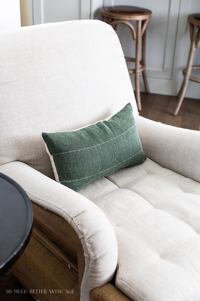Green small lumbar pillow on linen chair.