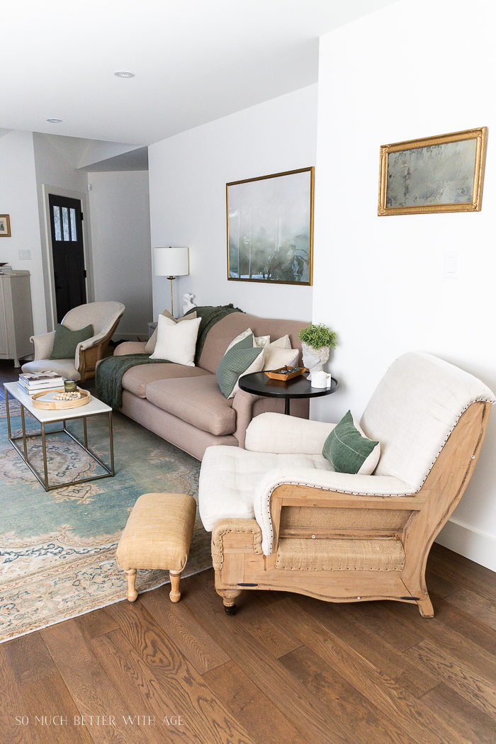 Living room with deconstructed chair, green rug and accents and marble and gold coffee table.