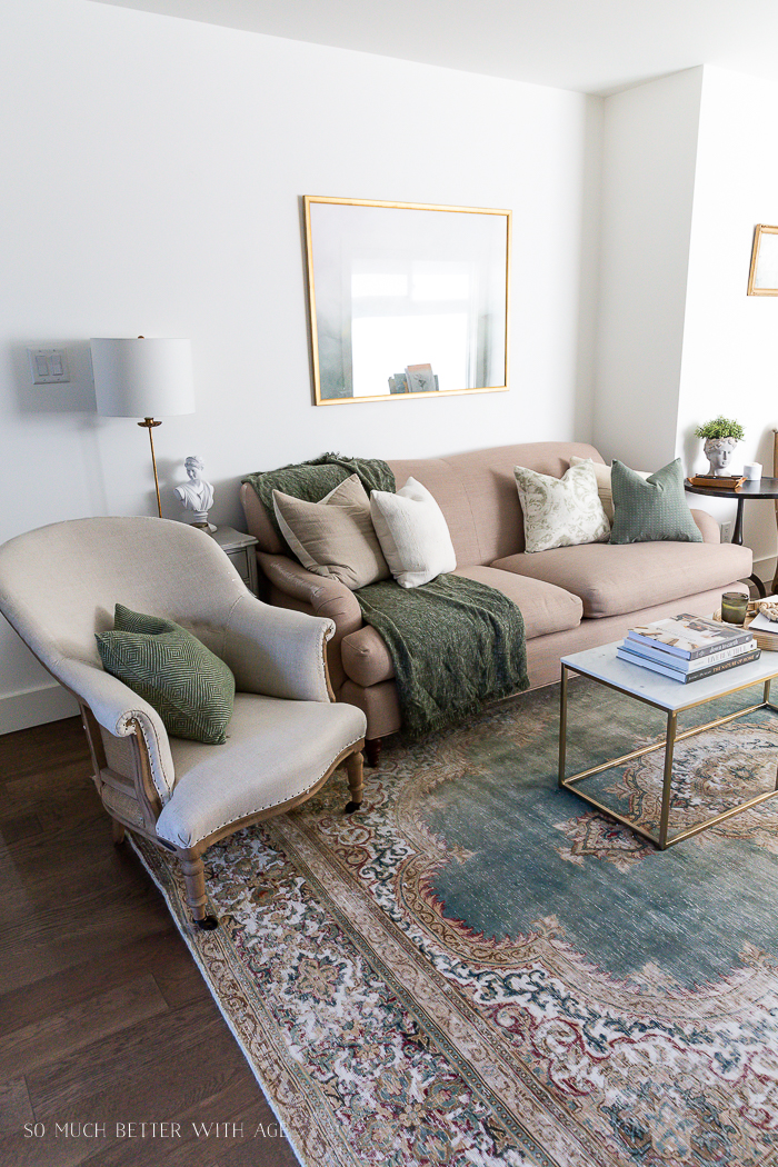 Beige English roll arm sofa with green vintage rug and deconstructed linen chair and marble and gold coffee table.
