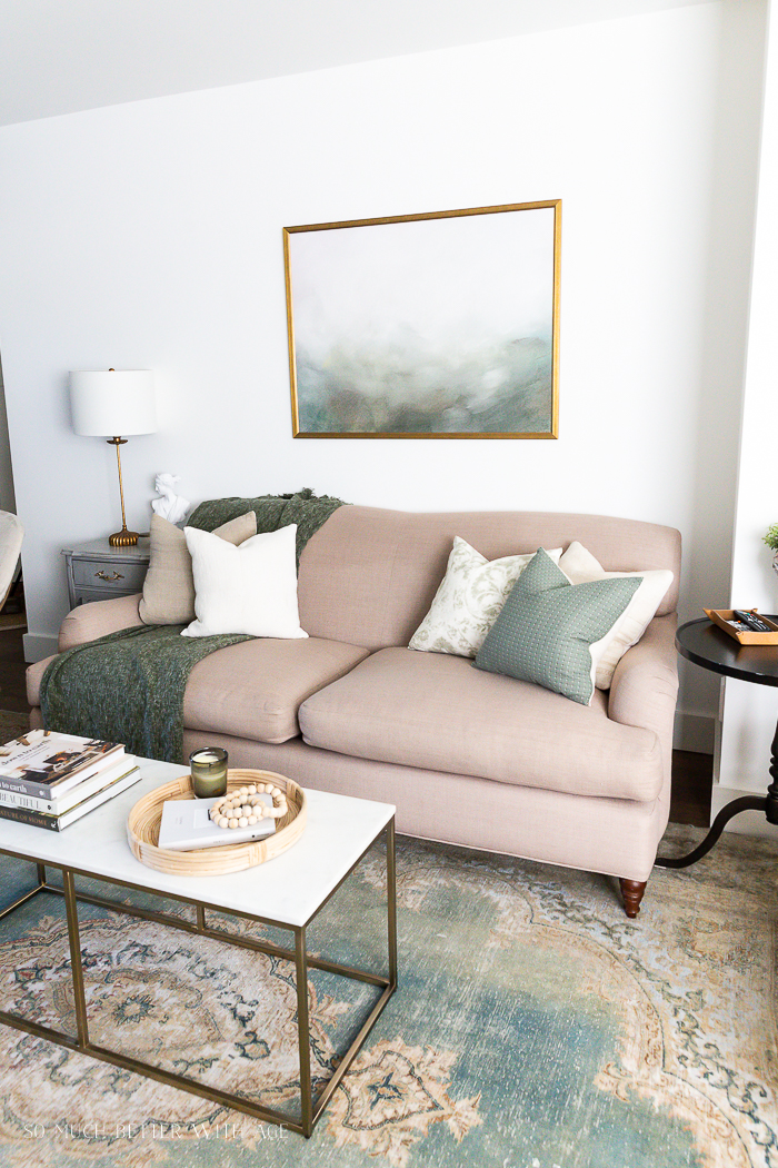English roll arm sofa with green accent pillows and green vintage rug.