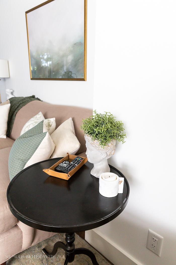 Statue head planter on black pedestal side table in living room.