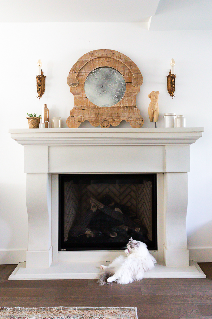 Cast stone fireplace with rustic antiqued mirror.