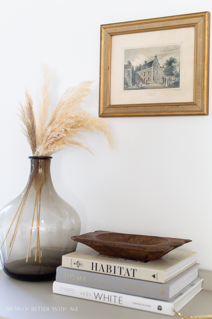 Coffee table/design books on cabinet with vintage art piece and large brown demijohn vase with pampas grass in it.