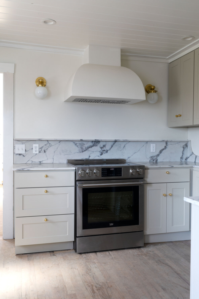 Mini gold wall sconces in small kitchen renovation by The Grit and Polish.