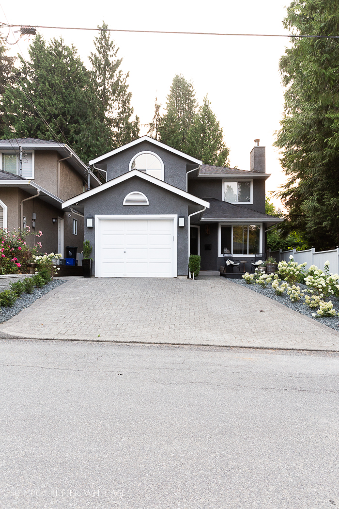 Grey house with white trim and garage door and limelight hydrangeas.
