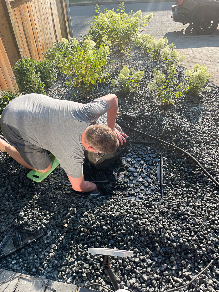 Installing water fountain vinyl tubing into water basin.