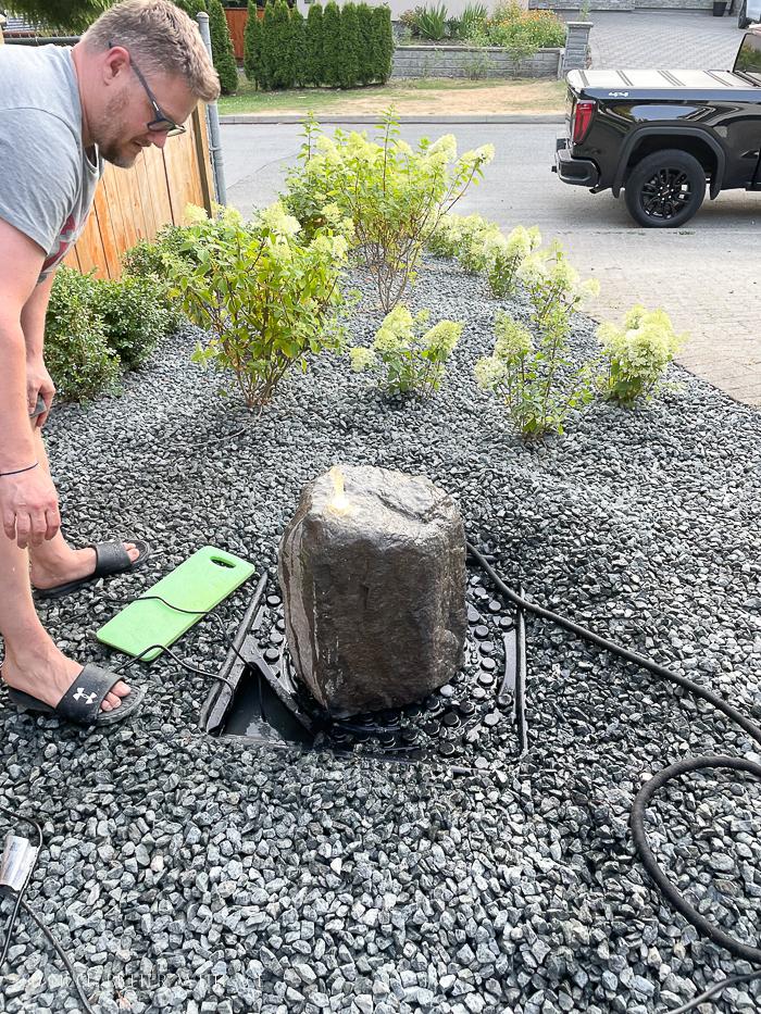 Installing basalt rock water fountain over Aquascape water basin.