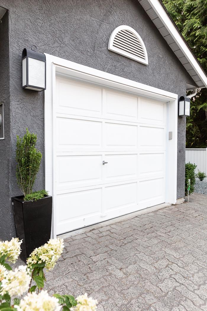 Grey house with white garage door with black ceramic planter.