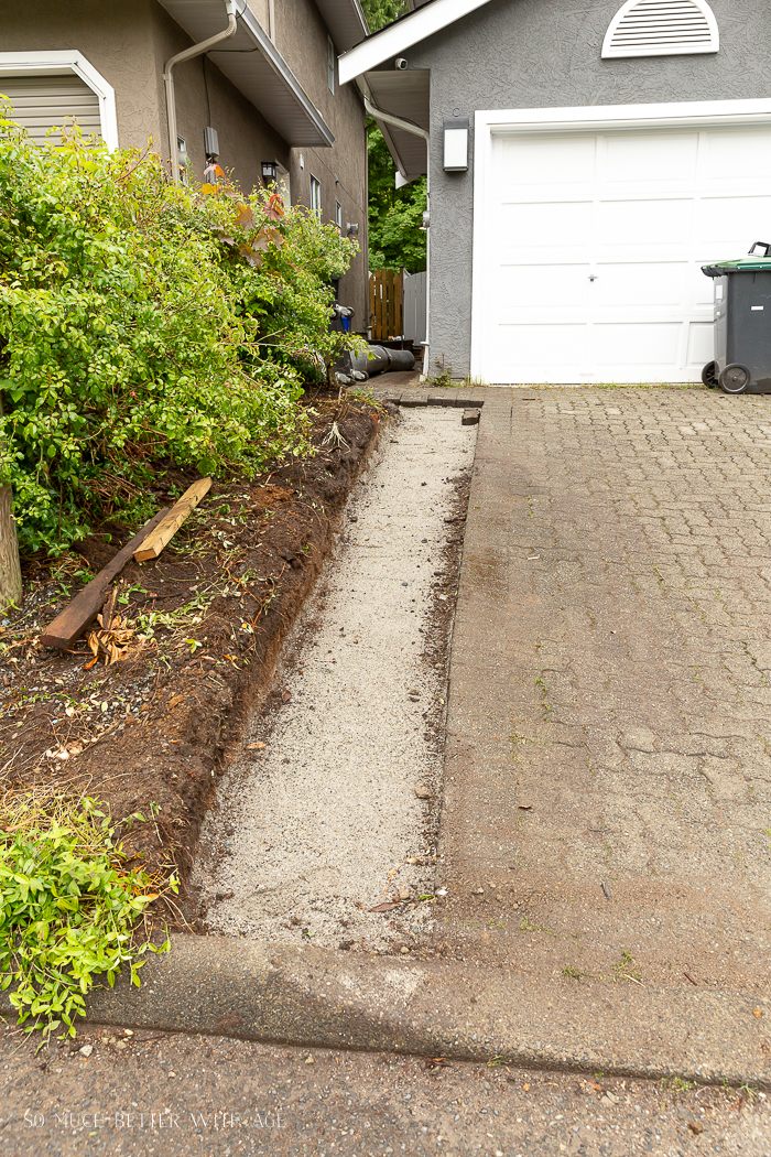 Extending the pavers on driveway of grey house.