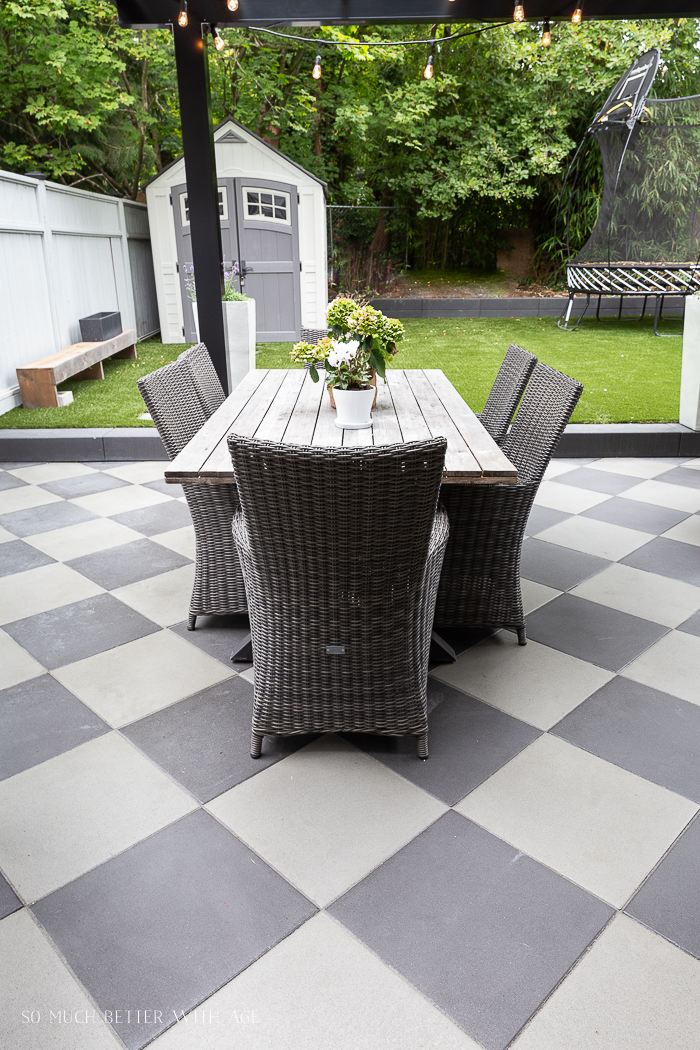 Dining table and chairs outside on checkerboard patio.